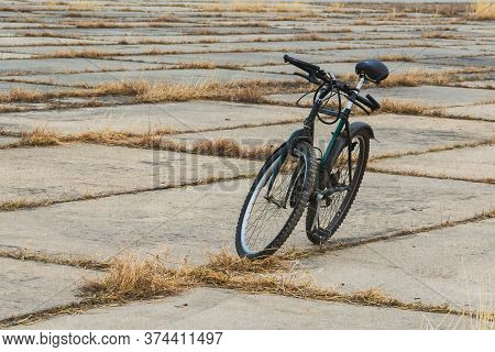 An Old Bicycle Stands In An Open Area, The Background Of An Abandoned Airfield With A Concrete Taxiw