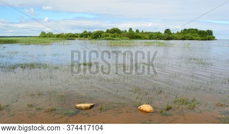 Transparent Water With A Visible Sandy Bottom, Stones And Green Algae At The Bottom Of The Reservoir