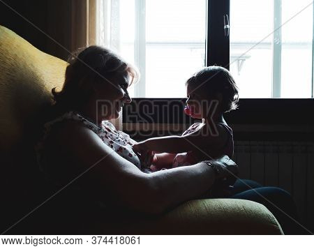 Little Girl With Pacifier Sitting On Grandmother's Legs In The Living Room At Home - Happy Middle-ag