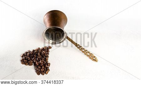 Coffee Beans And Turk On A White Scuffed Background. The Concept Of A Popular Invigorating Drink For
