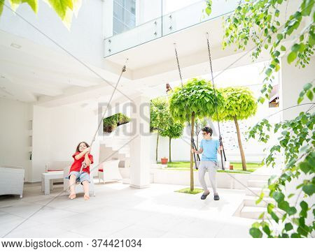 Two kids playing on the swing in a backyard of a villa