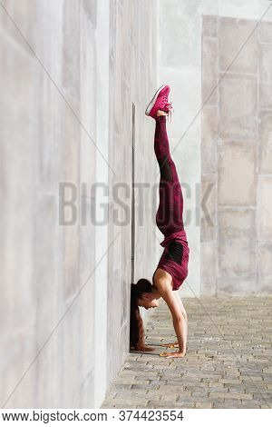 A Girl With A Sporty Build Performs A Handstand Exercise On A Street Playground