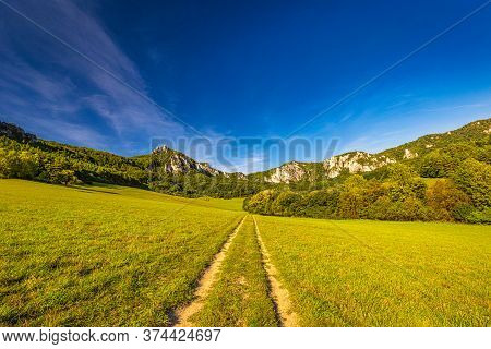 A Field Road Through The Valley Of Mountain Landscape With Rocky Peaks On Background In Summer Time.