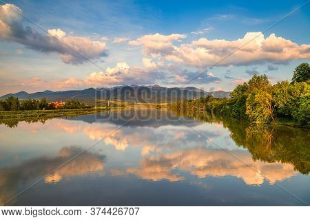 Mirroring Of The Mountainous Landscape On The Water Surface Of The Dam At Sunset. Zilina Dam In The