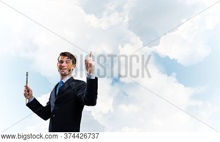 Happy And Young Businessman In Black Suit Holding Paintbrush In His Hand And Smiling While Standing