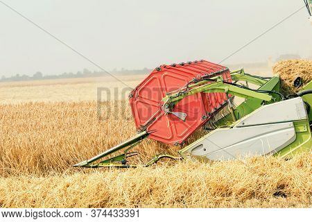 Closeup Combine Harvesting A Wheat Field. Combine Working The Field.