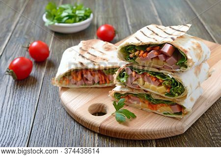 Lavash Rolls With Vegetables, Ham And Cheese. Tasty Breakfast Appetizer On A Wooden Board.