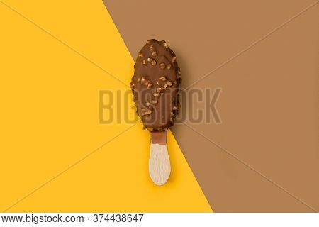 Chocolate Dipped Ice Lolly With Peanuts Chips On A Brown And Yellow Background