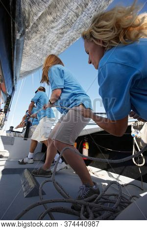 Sailing team pulling rope on yacht