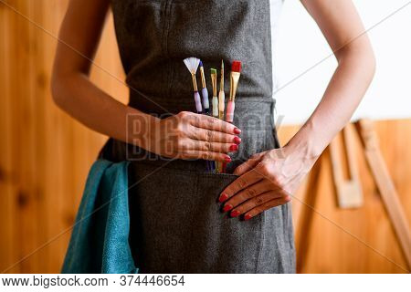 Close-up View Of Woman Who Holds Several Paint Brushes In Her Hand