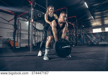 Beautiful Young Sporty Couple Training, Workout In Gym Together. Caucasian Man Training With Female