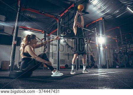 Beautiful Young Sporty Couple Workout In Gym Together. Caucasian Man Training With Female Trainer. C