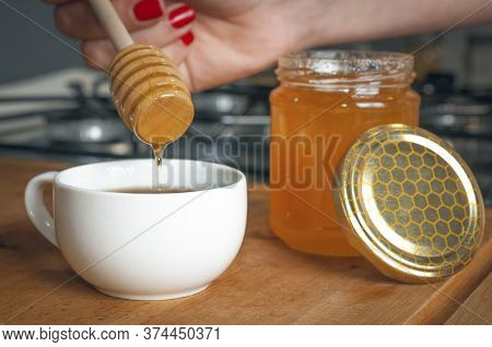 Woman Pour Honey Into A Cup Of Coffee As Sweetener