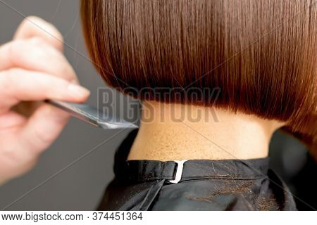 Hairdresser Combs Short Hair Of Brunette Woman Close Up In Hair Salon. Toned.