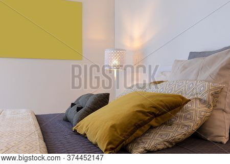 Detail of bed with many colored cushions. A cozy and warm bedroom.