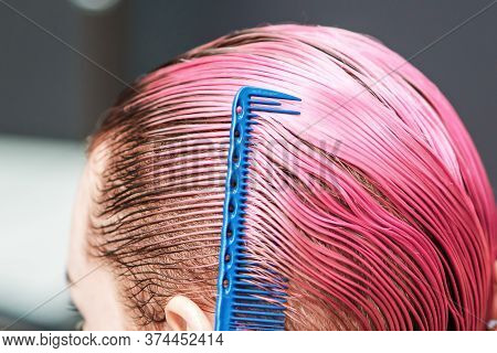 Hairdresser Hand Is Combing Wet Short Pink Hair Of Woman In Hair Salon, Close Up.