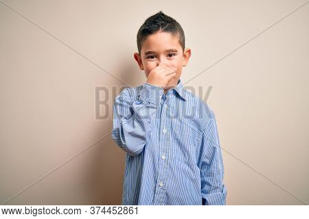 Young little boy kid wearing elegant shirt standing over isolated background smelling something stinky and disgusting, intolerable smell, holding breath with fingers on nose. Bad smell