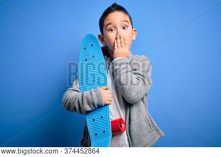 Young little boy kid skateboarder holding modern skateboard over blue isolated background cover mouth with hand shocked with shame for mistake, expression of fear, scared in silence, secret concept