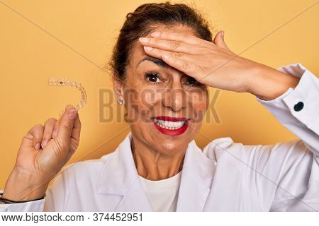 Middle age senior dentist woman holding clear aligner for teeth correction stressed with hand on head, shocked with shame and surprise face, angry and frustrated. Fear and upset for mistake.