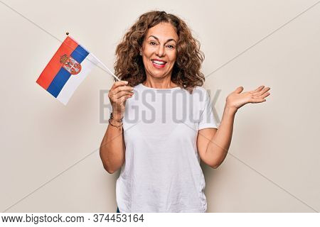 Middle age beautiful patriotic woman holding serbian flag over isolated white background celebrating achievement with happy smile and winner expression with raised hand