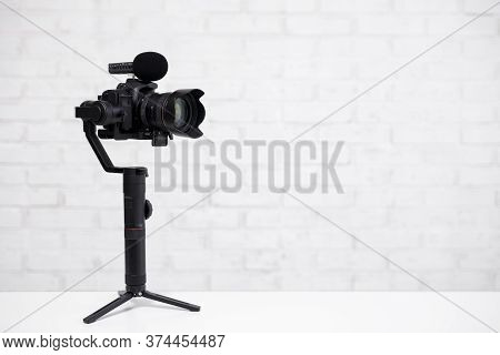Modern Dslr Camera On 3-axis Gimbal Stabilizer With Microphone Over White Brick Wall Background With