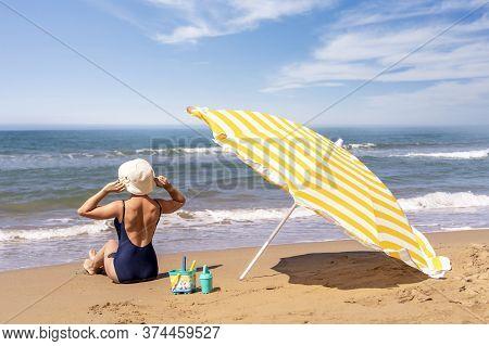 Beautiful Woman Sitting On Golden Fine Sand Enjoying The Idyllic Scene Of The Sun, Sand And Sea. Bea