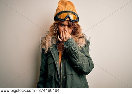 Young african american skier woman with curly hair wearing snow sportswear and ski goggles smelling something stinky and disgusting, intolerable smell, holding breath with fingers on nose. Bad smell