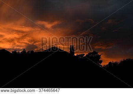 Silhouette Of Street Of Houses Exterior In Sunset With Dark Sky Behind Buildings