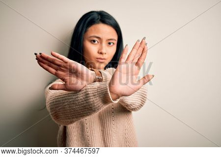 Young beautiful chinese woman wearing casual sweater over isolated white background Rejection expression crossing arms and palms doing negative sign, angry face