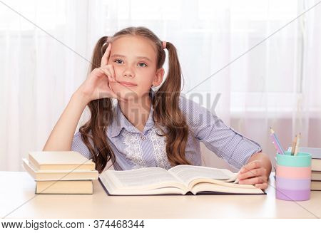 Education And School Concept. Cute Child Is Sitting At The Desk And Thinking. Cute Little Student Gi