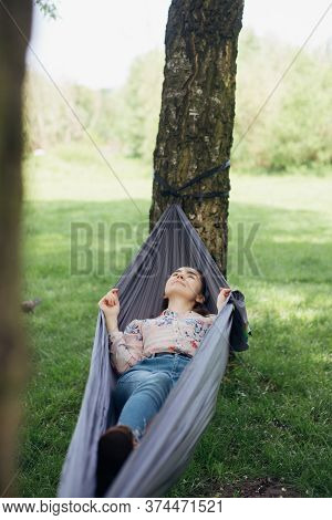 Young Woman Relaxing,  Chilling In Hammock Among Trees At Picnic In Summer Park. Social Distancing.