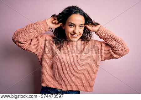 Young beautiful woman with curly hair wearing casual sweater over isolated pink background Smiling pulling ears with fingers, funny gesture. Audition problem