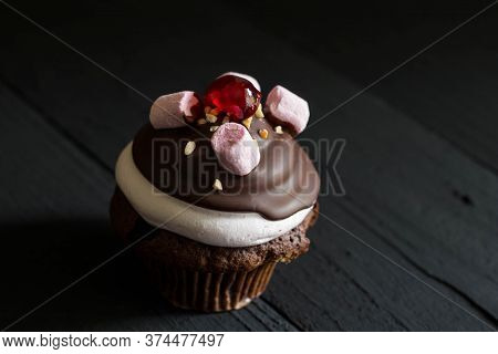 Decadent Marshmallow And Chocolate Coated Cupcake Isolated On Black Rustic Background With Space For