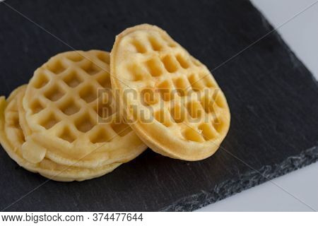 Round Small Waffles On Black Slate Background Waffles With Copy Space - Selective Focus