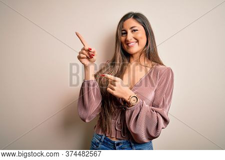 Young beautiful brunette elegant woman with long hair standing over isolated background smiling and looking at the camera pointing with two hands and fingers to the side.