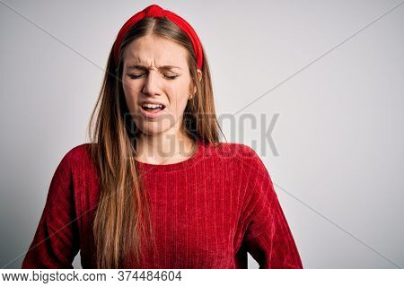 Young beautiful redhead woman wearing red casual sweater and diadem over yellow background with hand on stomach because nausea, painful disease feeling unwell. Ache concept.