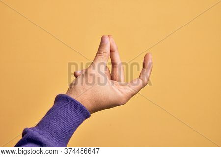 Hand of caucasian young man showing fingers over isolated yellow background snapping fingers for success, easy and click symbol gesture with hand