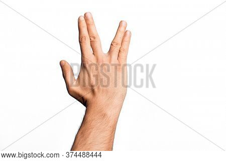 Hand of caucasian young man showing fingers over isolated white background greeting doing Vulcan salute, showing back of the hand and fingers, freak culture