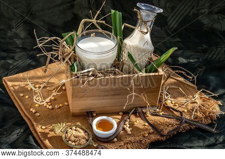 Soy Products : A Glass Of Homemade Soy Milk And Grains (soybeans) In Wooden Box Served With Brown Su