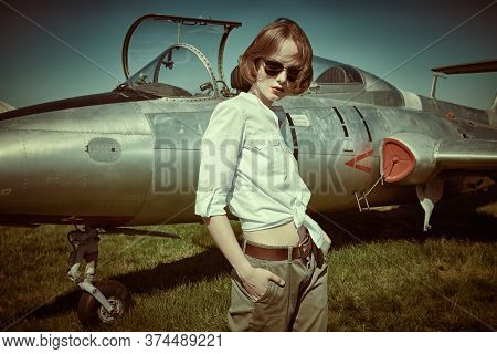 Portrait of a beautiful pilot girl posing next to her fighter plane at the airfield.