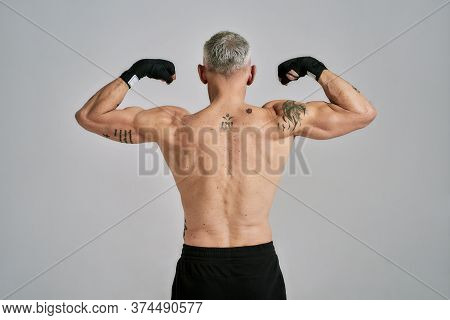 Half Naked Middle Aged Athletic Man, Kickboxer Showing His Body, While Exercising, Practicing Punche