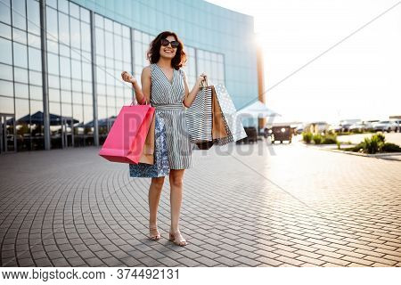 Young Beautiful Happy Woman Walks Out Of Shopping Mall With Purchases. Shopaholic Girl Glad To Buy C