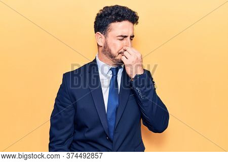Young hispanic man wearing suit smelling something stinky and disgusting, intolerable smell, holding breath with fingers on nose. bad smell