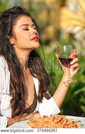 woman with red lips eat pasta. Hunger, appetite, recipe. Woman eating pasta in italian garden . Italian macaroni or spaghetti for dinner
