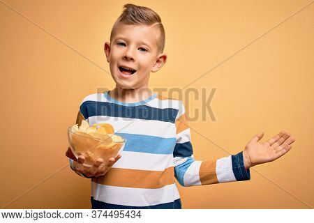 Young little caucasian kid eating unheatlhy potatoes crisps chips over yellow background very happy and excited, winner expression celebrating victory screaming with big smile and raised hands