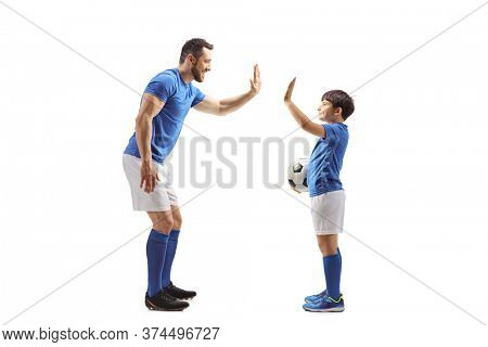 Full length profile shot of an adult football player gesturing high five with a junior football player isolated on white background