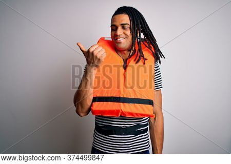 Young african american afro man with dreadlocks wearing orange lifejacket smiling with happy face looking and pointing to the side with thumb up.
