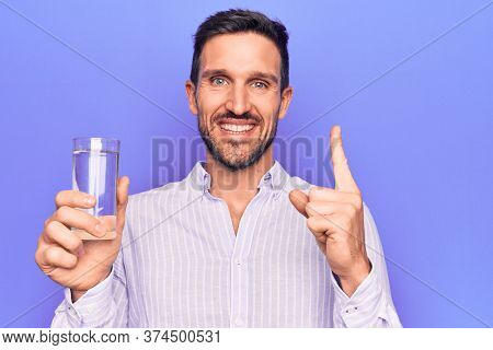 Young handsome man drinking glass of water to refreshment over isolated purple background smiling with an idea or question pointing finger with happy face, number one