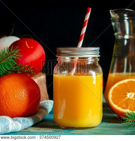 Christmas Cocktail. Orange Fresh In A Glass Jar With A Tube Stands On A Wood Table Next To Christmas