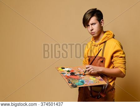 Young Painter In Yellow Hoodie And Jumpsuit Standing And Holding Easel, Paint And Brush In Hands Ove